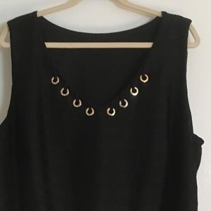 Black sleeveless top with gold trim.